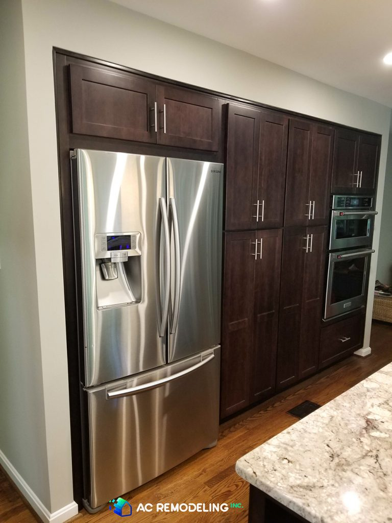 custom dark wood cabinets with large silver refrigerator